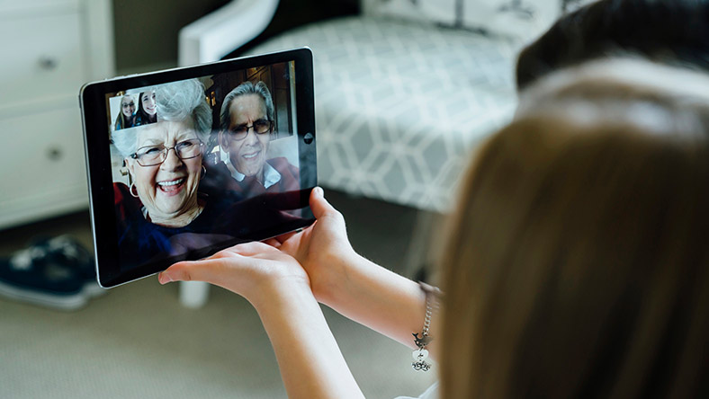 Two young women use a mobile tablet to enjoy a video call with their grandparents.
