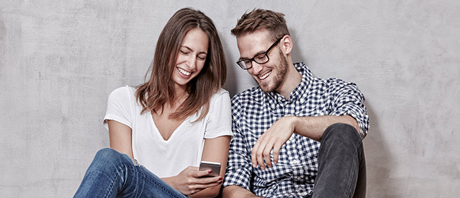 Young couple sitting against a grey wall looking at the mobile phone laughing