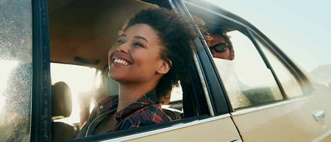 Young lady sitting in the front car seat with the window down and smiling