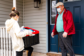 A woman wearing a mask dropping off a box for an older man, also wearing a mask.