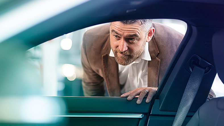 Man looking through car window to admire its interior