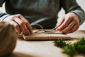 Close up photo of two hands wrapping a Christmas gift with brown paper and twine.
