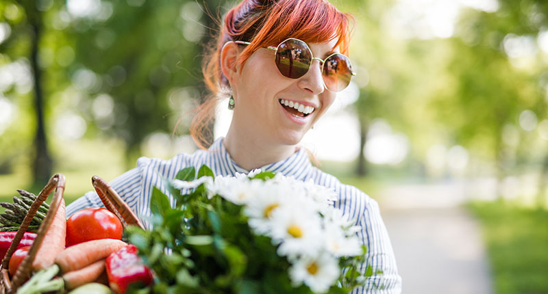 How to be sustainable - image of laughing girl wearing sunglasses carrying fresh fruit and flowers