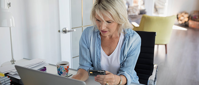 Woman with a credit card and laptop.