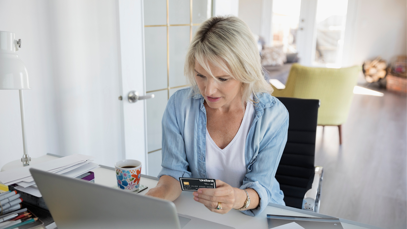 Middle-aged woman at home making a payment online, looking at card in hand and laptop screen