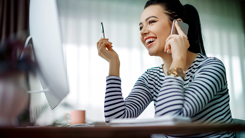 Young woman on the phone looking at computer and smiling