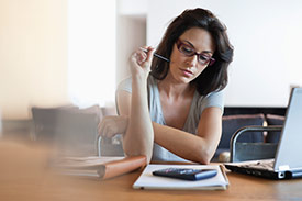 A woman with dark hair and glasses trying to decide between an overdraft and a personal loan while sitting at her desk.