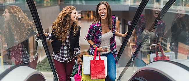 two women with shopping bags going up escalators