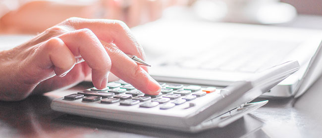 A man typing on a calculator - tax tips for students