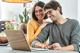 Your credit report - image of smiling couple sitting together in front of a laptop in a stylish apartment