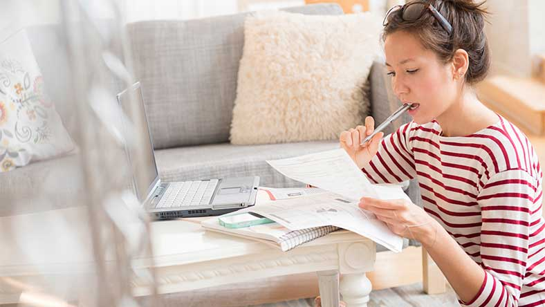 Woman sitting at coffee table calculating home loan expenses