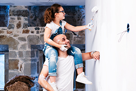 Dad with daughter on his shoulders painting a wall