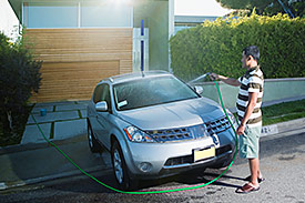 Man cleaning car with hose in his driveway