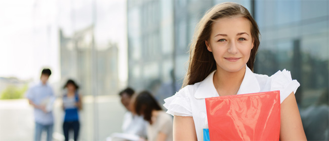 A young woman holding a folder and looking at the camera.