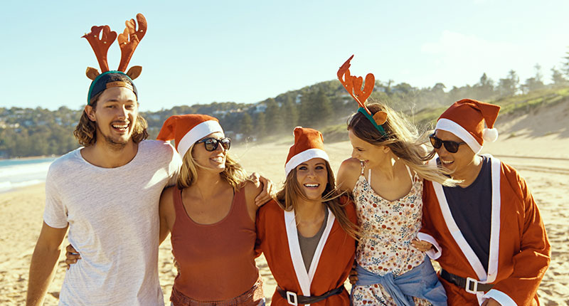 Tips for stress free Christmas travel - image of friends having fun on the beach wearing Santa outfits