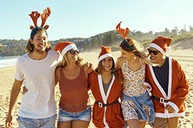 Tips for stress free Christmas travel - image of friends wearing Santa hats on the beach