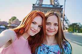 Two young women posing for a selfie in front of the Eiffel Tower